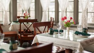 bright room with dining tables, flowers, windows